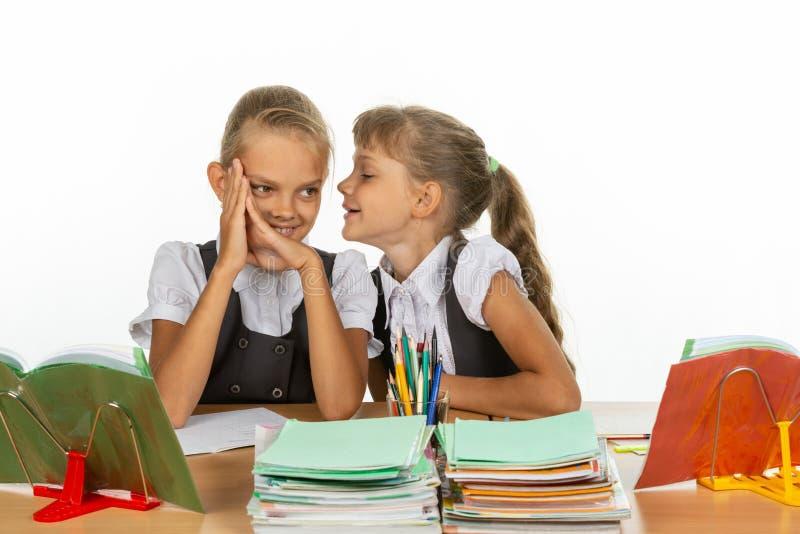 La novia en el escritorio de la escuela dice algo interesante en el oído fotos de archivo libres de regalías