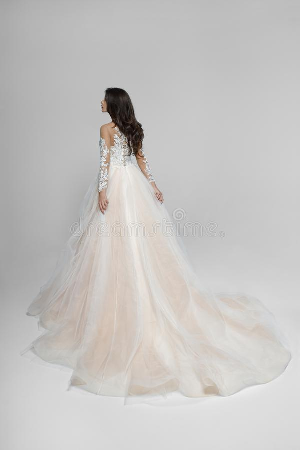 La novia en el estudio en un vestido que se casaba largo hermoso del color ligero del melocot?n dio vuelta detr?s, aislado en un  fotos de archivo libres de regalías