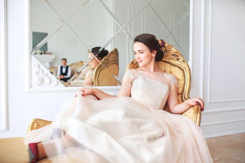 La novia en el vestido hermoso que se sienta en el sofá dentro en el interior blanco del estudio tiene gusto en casa Estilo de mo fotos de archivo