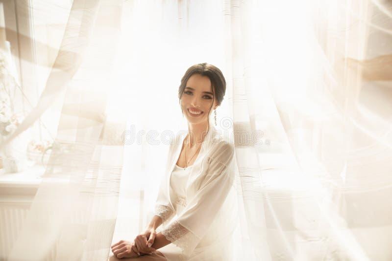 La novia en el vestido hermoso que se sienta en silla dentro en el interior blanco del estudio tiene gusto en casa Tiro de moda d imágenes de archivo libres de regalías