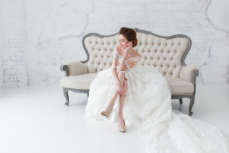 La novia en el vestido largo que se sienta en el sofá dentro en el interior blanco del estudio tiene gusto en casa Tiro de moda d imagen de archivo