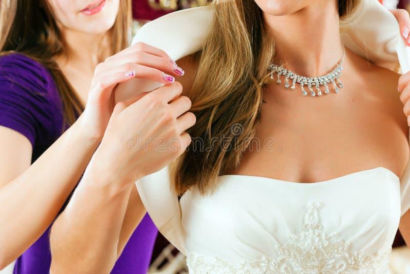 La novia en la ropa hace compras para las alineadas de boda imagenes de archivo