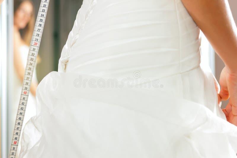 La novia en la ropa hace compras para las alineadas de boda imagen de archivo