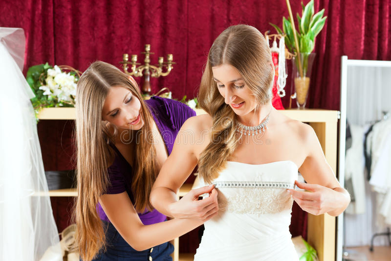 La novia en la ropa hace compras para las alineadas de boda foto de archivo