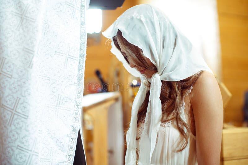 La novia en un mantón blanco ruega ante un sacerdote que se coloca en el kne imagen de archivo libre de regalías