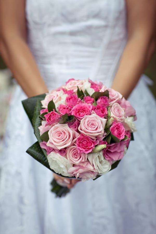 La novia en un vestido blanco hermoso está sosteniendo un ramo colorido de la boda de rosas rosadas, blancas, y púrpuras foto de archivo libre de regalías