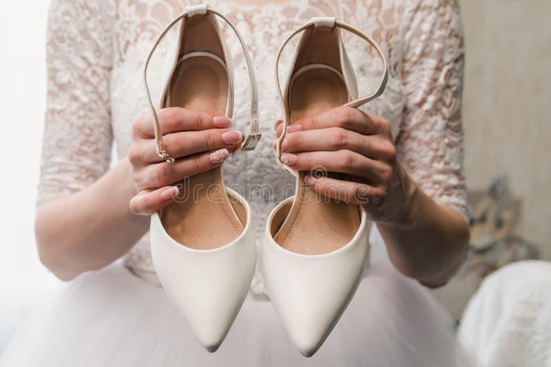 La novia en un vestido que se casa sostiene los zapatos blancos en manos bien arregladas con una manicura hermosa foto de archivo libre de regalías