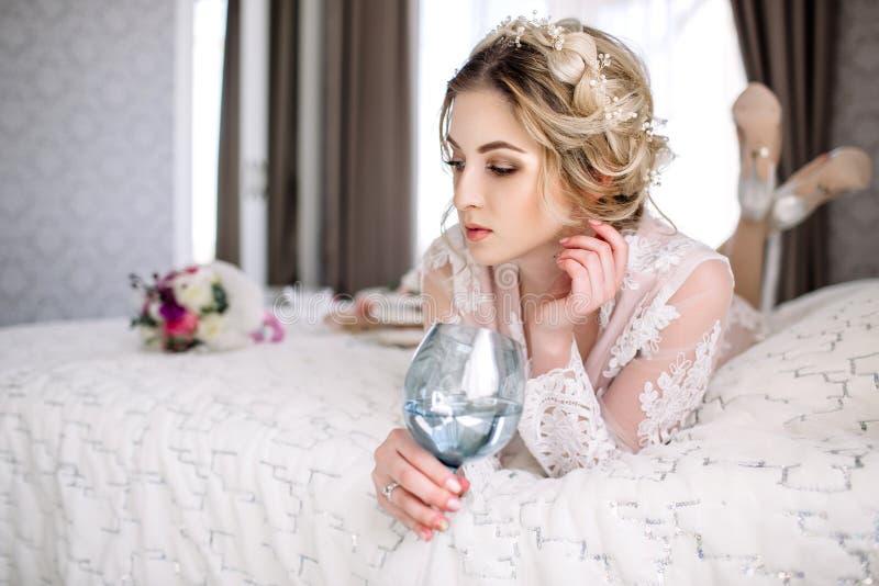La novia en una albornoz a la ventana del dormitorio por la mañana imagen de archivo