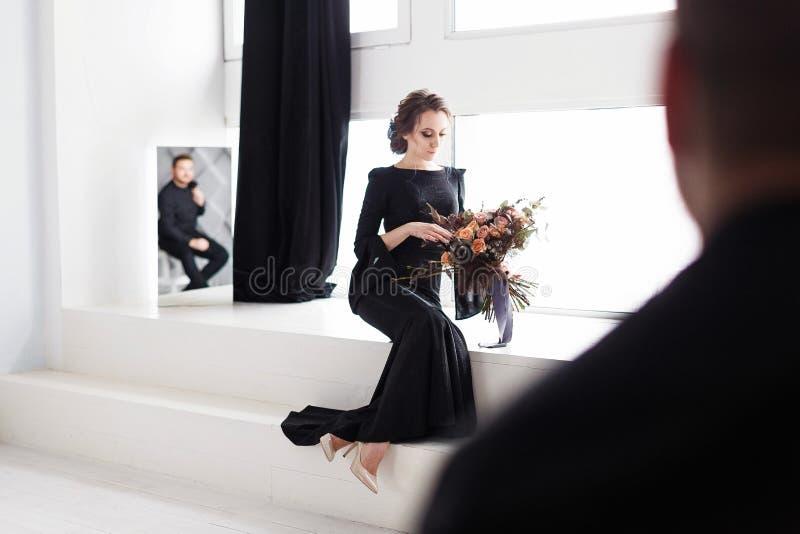 La novia en vestido negro Reflejo en el espejo Sitio blanco del estudio con las ventanas Tiro horizontal con el novio borroso imágenes de archivo libres de regalías