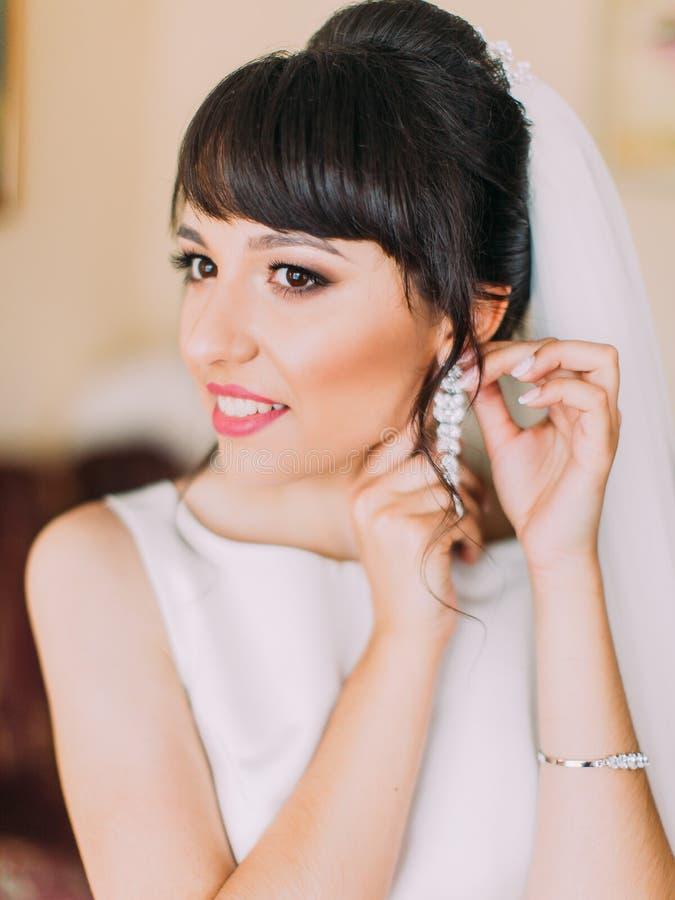 La novia encantadora está poniendo los pendientes de plata largos imágenes de archivo libres de regalías