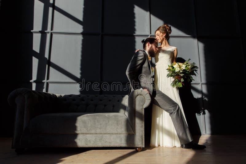 La novia está abrazando al novio que se sienta en el brazo del sofá Son encendidos por la luz dura de la ventana imagen de archivo