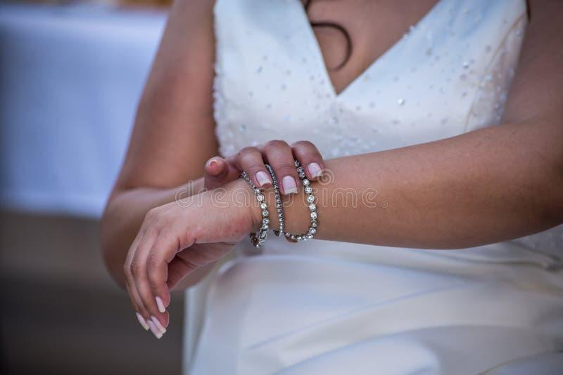 La novia está fijando su pulsera, primer, luz del día, ninguna cara imagen de archivo libre de regalías