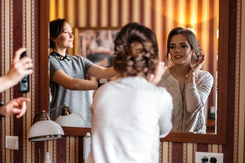 La novia feliz admira su reflexión en el espejo El peluquero termina hacer el peinado para ella foto de archivo libre de regalías