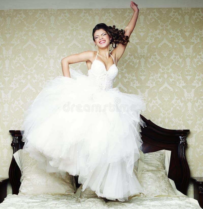 La novia feliz salta en cama. imagen de archivo