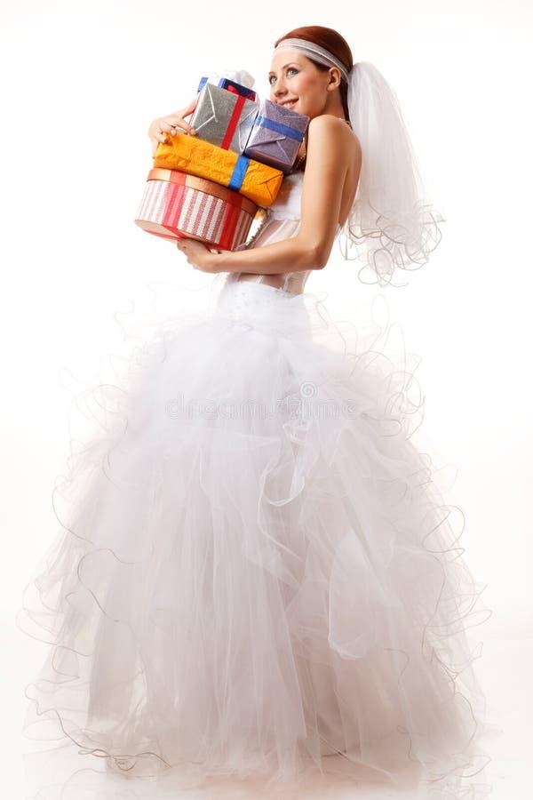 La novia feliz sostiene la cadera de regalos foto de archivo