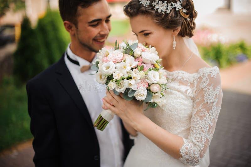 La novia goza del olor de un ramo de la boda, los soportes del novio al lado de la sonrisa imagenes de archivo