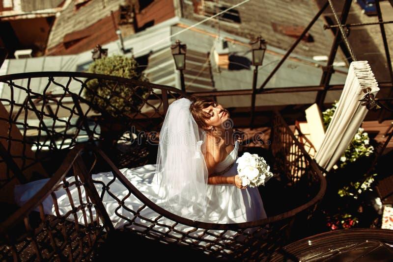 La novia goza del sol del verano que se coloca en las escaleras espirales en el roo foto de archivo