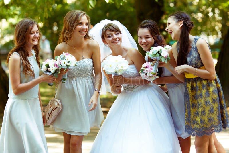 La novia habla con las damas de honor que presentan en el parque fotografía de archivo