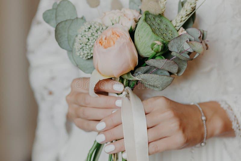 La novia hermosa con el ramo agradable se prepara para la ceremonia de boda El control de las manos de las novias florece interio imagen de archivo