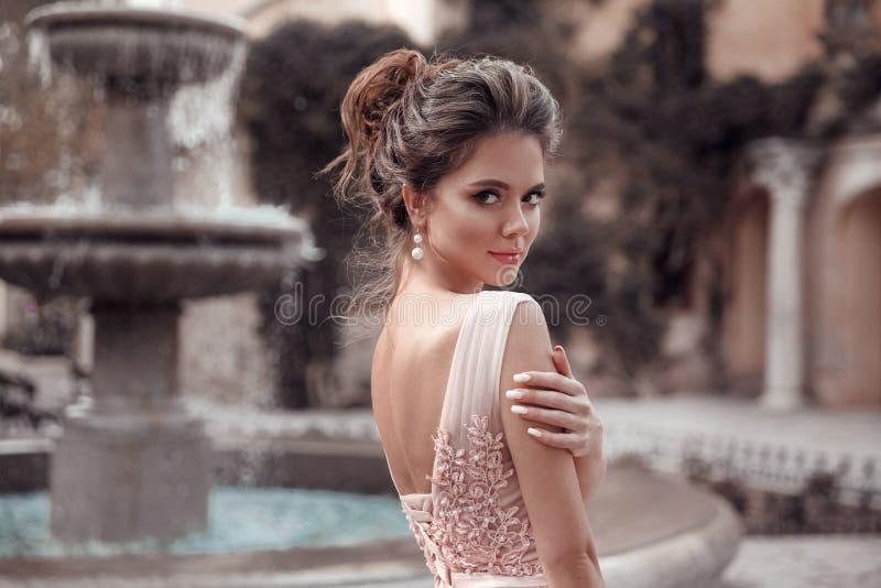 La novia hermosa con joyería de los pendientes de la perla lleva el vestido rosado del baile de fin de curso Retrato romántico al foto de archivo