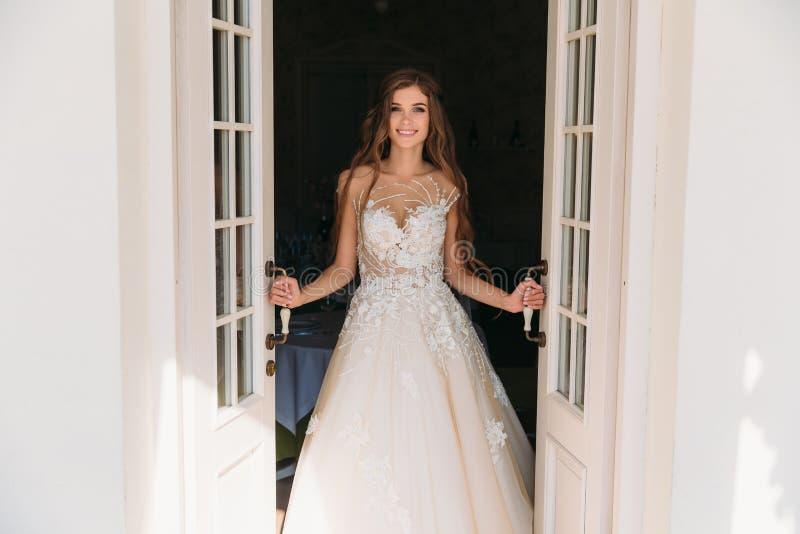 La novia hermosa con los pelos largos atractivos se coloca cerca de las puertas blancas La mujer bastante joven en el vestido bla imagen de archivo
