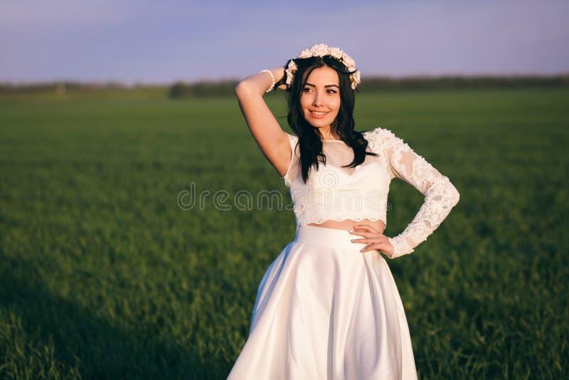 La novia hermosa, de moda presenta en un campo, con el pelo negro en el cual se trenza una guirnalda floral imagen de archivo