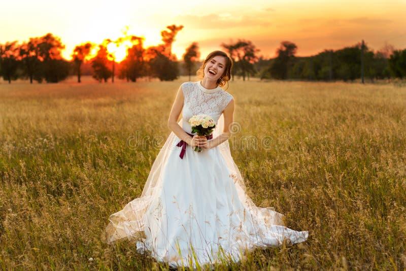 La novia hermosa en vestido de boda ríe y sostiene el ramo en manos en la puesta del sol imagen de archivo