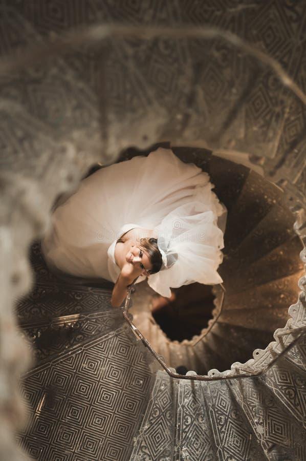 La novia hermosa en vestido magnífico se coloca solamente en las escaleras foto de archivo