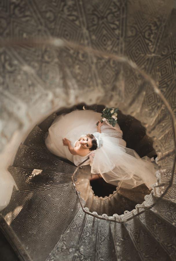 La novia hermosa en vestido magnífico se coloca solamente en las escaleras fotos de archivo