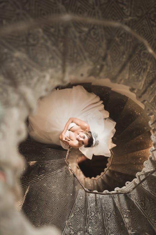 La novia hermosa en vestido magnífico se coloca solamente en las escaleras imagenes de archivo