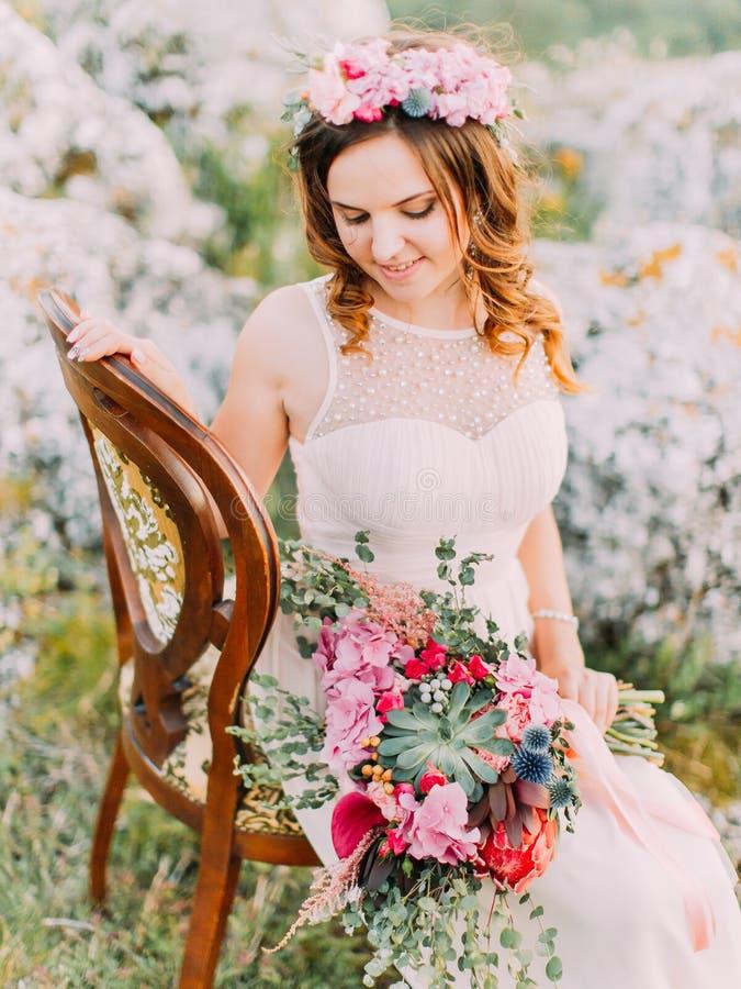 La novia hermosa está mirando el ramo de la boda mientras que se sienta en la silla en las montañas imágenes de archivo libres de regalías