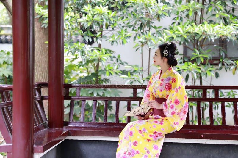 La novia hermosa japonesa asiática tradicional de la mujer del geisha lleva el control del kimono que una fan se sienta en un pab imagen de archivo libre de regalías