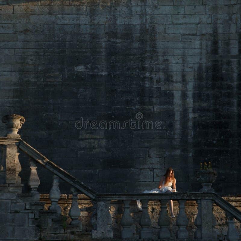 La novia hermosa se está sentando al borde de balcón fotografía de archivo
