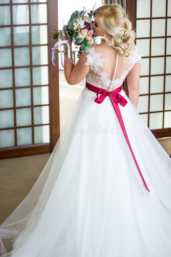 La novia hermosa sostiene suavemente el ramo de la boda del vintage del wer imagen de archivo libre de regalías
