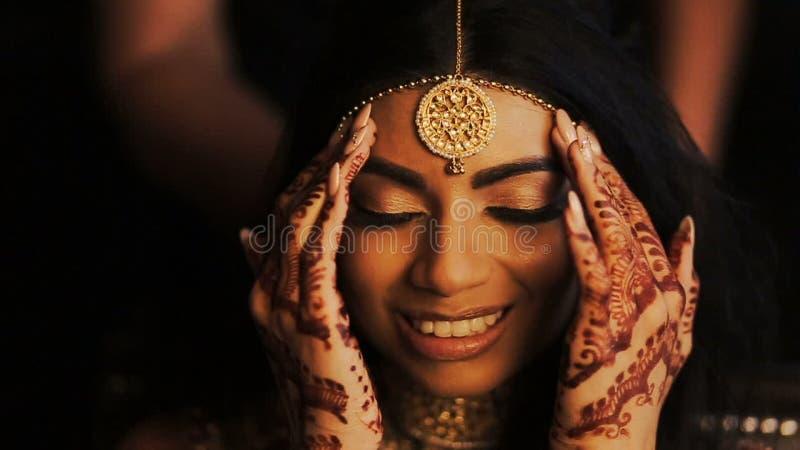 La novia india magnífica toca los accesorios de oro en su cabeza metrajes