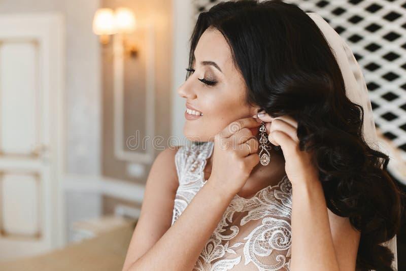 La novia joven hermosa con casarse el peinado y con maquillaje de moda pone en su pendiente en interior de lujo clásico imagen de archivo libre de regalías