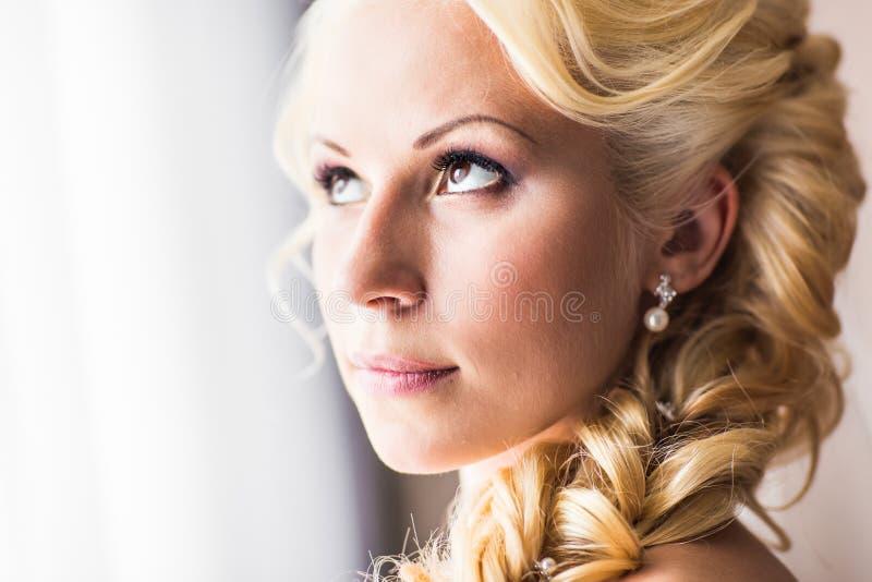 La novia joven hermosa con maquillaje de la boda y el peinado en dormitorio, mujer atractiva del recién casado tienen preparación fotografía de archivo