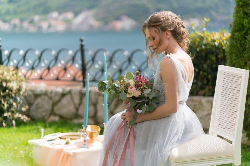 La novia joven hermosa en un césped presenta para la foto fotos de archivo libres de regalías