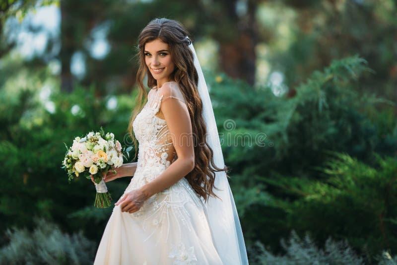 La novia joven linda con los pelos largos que sostienen su ramo de la boda incluye las rosas blancas y otras flores Blanco hermos fotos de archivo libres de regalías