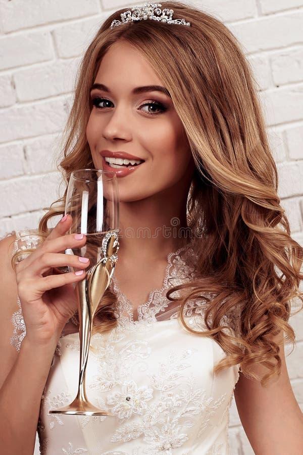 La novia joven magnífica con el pelo rizado rubio, lleva el vestido de boda y la corona elegantes fotos de archivo