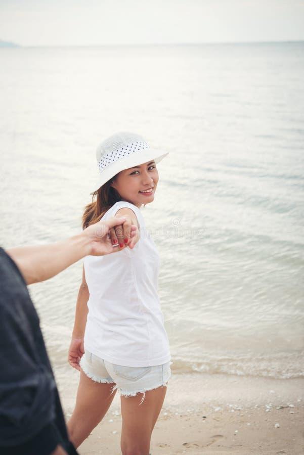 La novia le lleva novios a la playa Mujer que lleva a cabo su m imagen de archivo