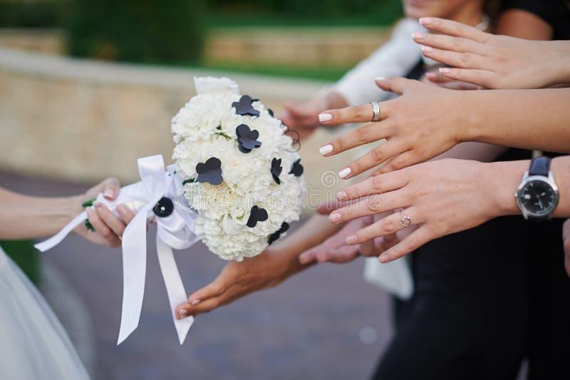 La novia lleva a cabo un ramo y las manos de la boda que alcanzan para él foto de archivo libre de regalías