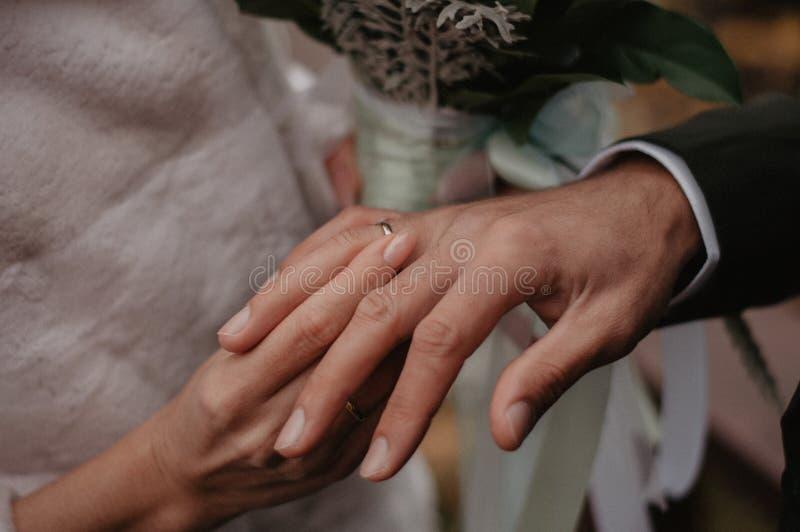 La novia lleva el anillo de bodas del oro en el finger del novio fotografía de archivo libre de regalías