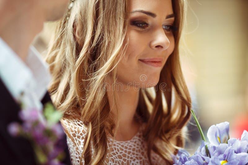 La novia mira la colocación encantadora detrás de un novio imagen de archivo