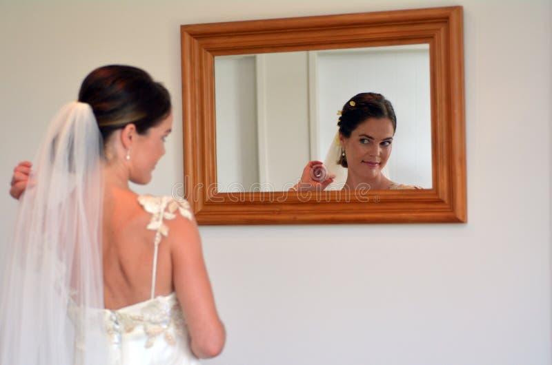 La novia mira se en el espejo en su día de boda imagen de archivo