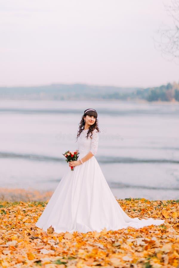 La novia pensativa inocente hermosa en vestido blanco magnífico se coloca en las hojas caidas en la orilla imagen de archivo libre de regalías