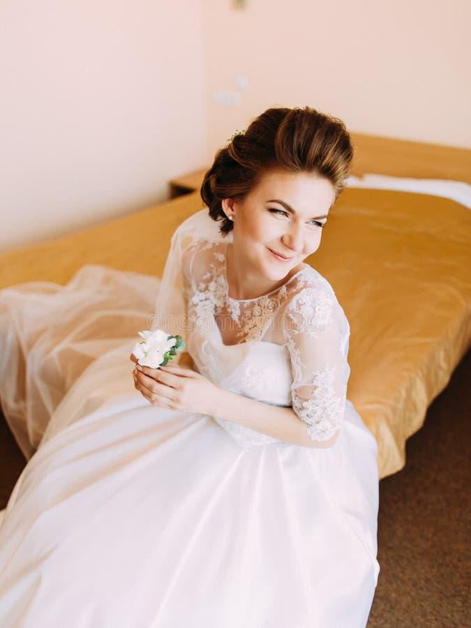 La novia que mira al lado derecho se está sentando en la cama y está sosteniendo el mini-ramo blanco fotografía de archivo