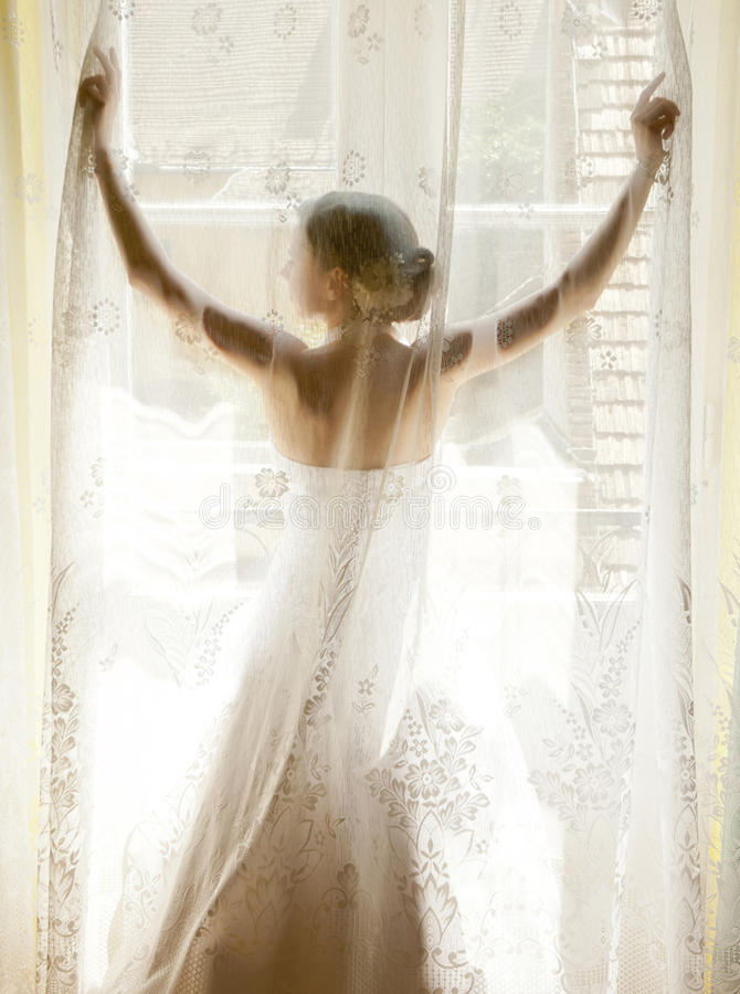 La novia que se coloca en la ventana fotos de archivo