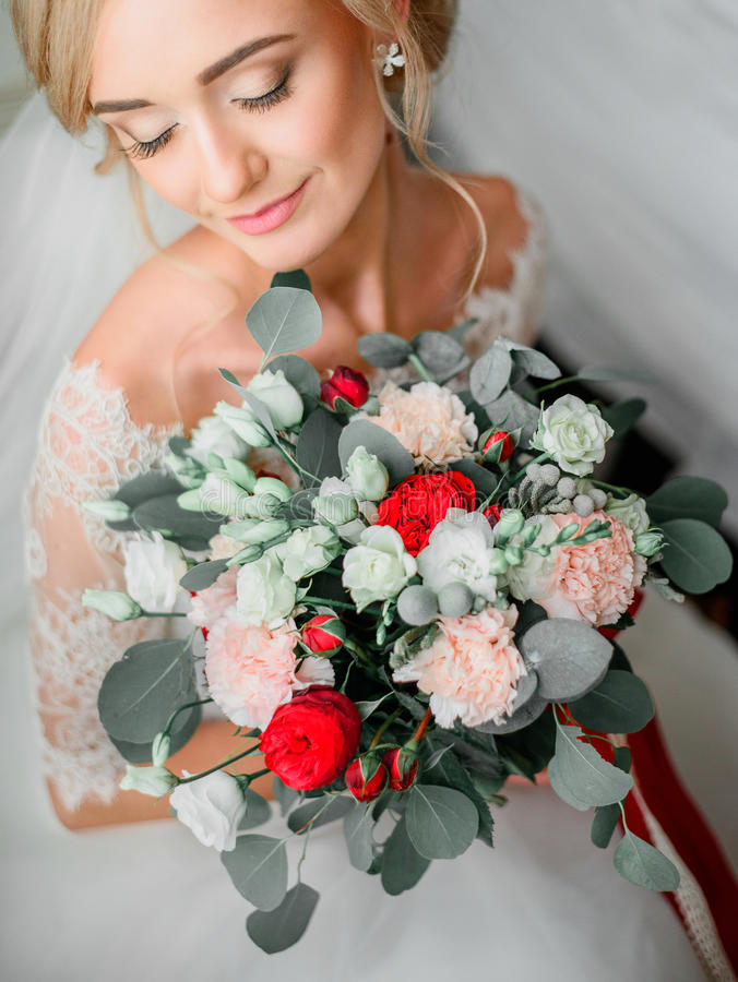 La novia rubia hermosa sostiene el ramo de la boda de rosas fotos de archivo
