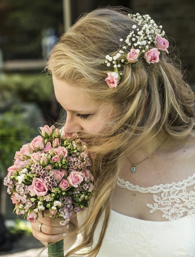 La novia rubia inhala el aroma del olor de un ramo de la flor de las rosas que se sostienen durante boda de la boda fotos de archivo